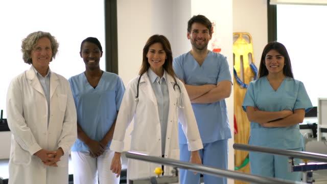 vídeos de stock, filmes e b-roll de equipe diversa dos orthopedists, dos terapeutas e dos enfermeiros em uma clínica de reabilitação física que enfrenta a câmera alegremente - physical injury