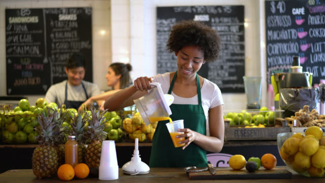 Diverse team working at a juice bar and woman at the front making a juice with an electrical juicer serving it and looking to the camera