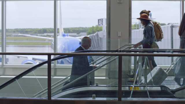 vídeos y material grabado en eventos de stock de slo mo. diverse travelers pass along stairwell in airport terminal near gate. - comunidad global