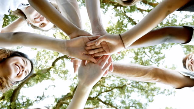 diverse volunteer group with hands in huddle before community project - community stock videos & royalty-free footage