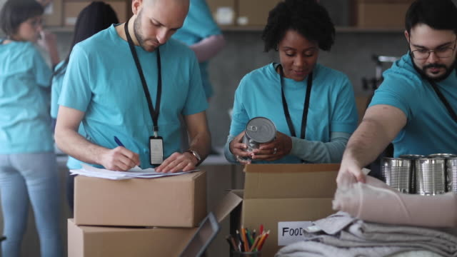 diverse volunteers packing donation boxes in charity food bank - charitable donation stock videos & royalty-free footage