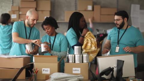 vídeos y material grabado en eventos de stock de diversos voluntarios empacando cajas de donación en banco de alimentos de caridad - voluntario