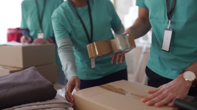 diverse volunteers packing donation boxes in charity food bank - charity and relief work stock videos & royalty-free footage