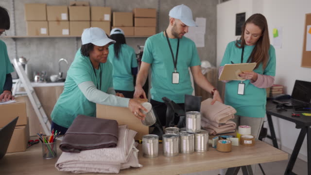 diverse volunteers packing donation boxes in charity food bank - altruism stock videos & royalty-free footage