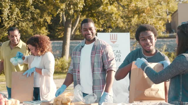 diverse volunteers sort through food donations during outdoor food drive - social services stock videos & royalty-free footage
