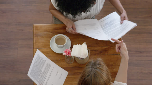 diverse women enjoying coffee while discussing business using some documents - coffee variation stock videos & royalty-free footage