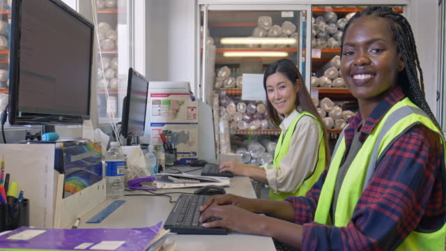 Diverse women working with the computer on deliveries at warehouse
