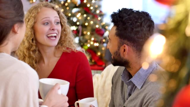 Diverse young adults enjoy a cup of coffee while talking during Christmas celebration