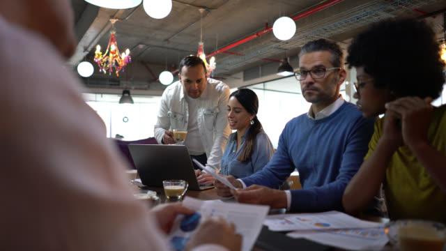 vielfältige junge gruppe von arbeitern in einem coworking-büro in einem treffen, in dem etwas diskutiert wird, während man warme getränke genießt - coworking stock-videos und b-roll-filmmaterial
