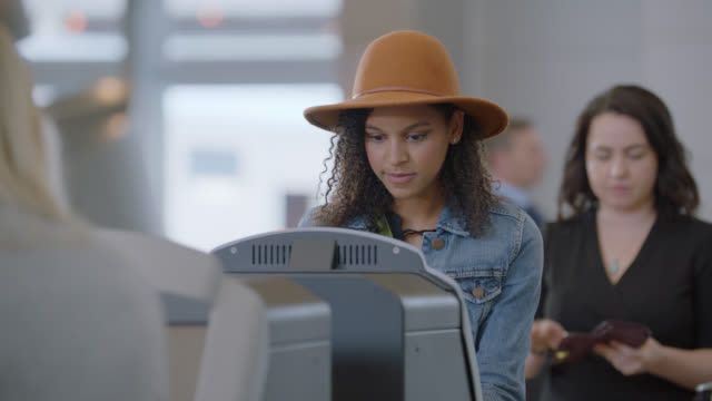 vídeos y material grabado en eventos de stock de diverse young woman uses self check-in kiosk while businesswoman waits in line behind. - entrada