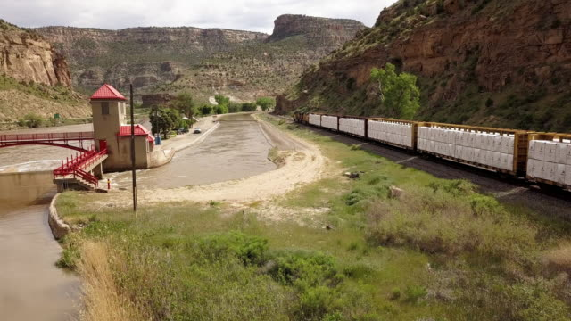 a diversion dam on the colorado river diverting water to create an irrigation canal system for farming and ranching with a freight train speeding past - irrigation equipment stock videos & royalty-free footage