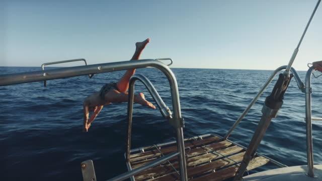 vídeos de stock e filmes b-roll de diving from a yacht sailboat cruising the sea - veículo aquático