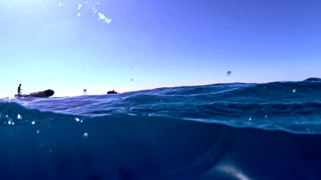 vídeos y material grabado en eventos de stock de sumergirse en el mar profundo. saltar desde un bote - perspectiva desde una barca