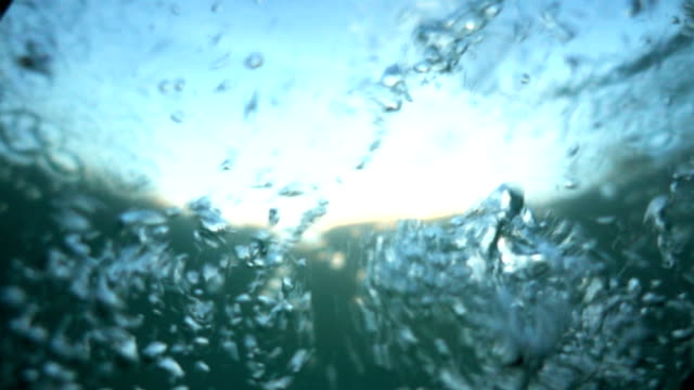 diving into the water. falling into the water in slow motion. different-sized bubbles in foaming turquoise water. sinking. version1. - moving image stock videos & royalty-free footage