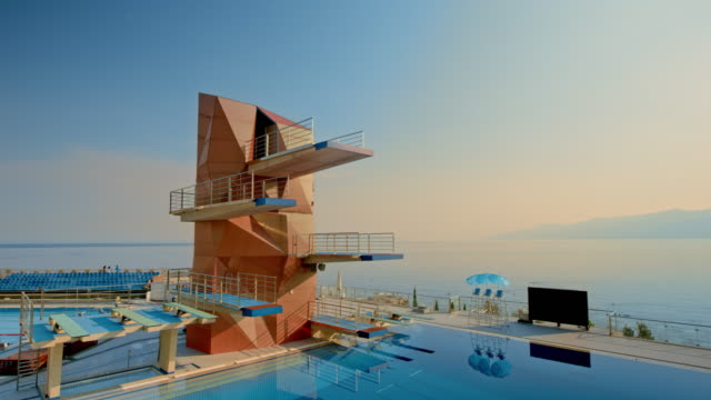 cs diving platforms above a calm pool overlooking the sea in the distance at sunset - crane shot stock videos & royalty-free footage