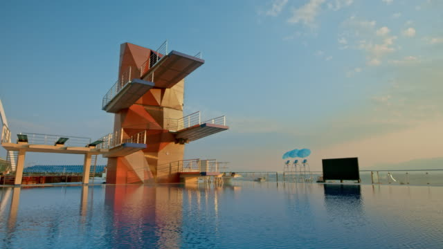cs diving tower above the calm water surface of the pool at sunset - crane shot stock videos & royalty-free footage