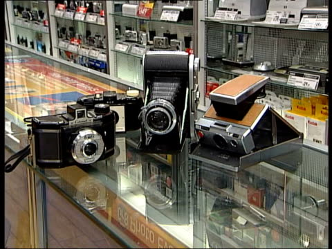 dixons store int display of 35mm cameras on counter display of digital cameras on counter sales assistant talking to female customer about digital... - digital camera stock videos and b-roll footage