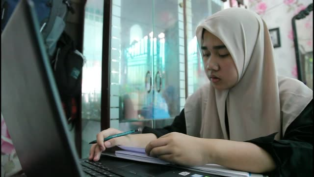 diza laila 18 years old an indonesian student who was repatriated from wuhan city took part in an online class from home using laptops and smart... - studying stock videos & royalty-free footage