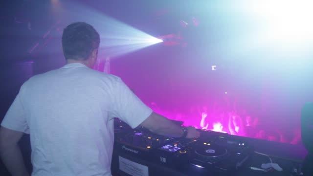 dj playing busy edm dance nightclub people dancing music club dj night rave club - dj stock videos & royalty-free footage
