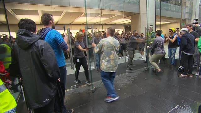 City PAN PEOPLE QUEUED OUTSIDE APPLE STORE AND POLICE / CROWDS GATHERED CHANTING COUNTDOWN TO DOORS OPENING CHEERING / FIRST CUSTOMER LET INTO STORE...