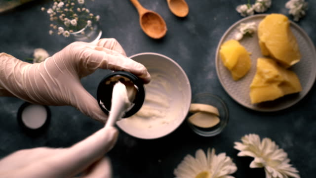 do it yourself - making of homemade organic hand cream - filling empty cup with cream with porcelain spoon then closing box - raw food stock videos & royalty-free footage