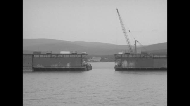 ws dock in two sections crane on one section / section with crane moves away / pan around battlecruiser seydlitz lying on side partially submerged /... - ship stock videos & royalty-free footage