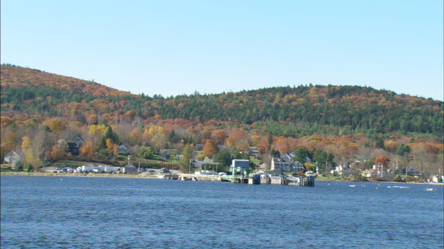 bobbing dock off coast of island in penobscot bay island w/ hills trees clear blue sky bg blue bay waters fg - augusta maine stock videos & royalty-free footage