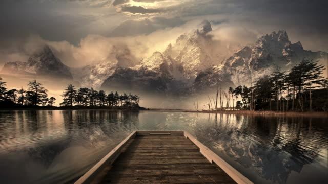 dock on lake reflecting rocky mountains, wyoming - 魔術師点の映像素材/bロール