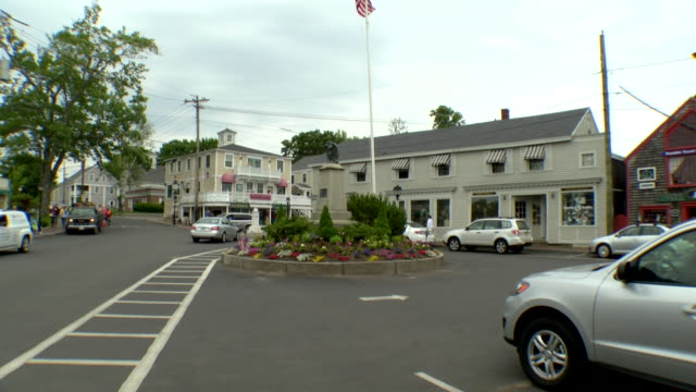 dock square with american flagpole and flowers amid median, small shops and storefronts with pedestrians milling about and traffic passing by - median nerve stock videos & royalty-free footage