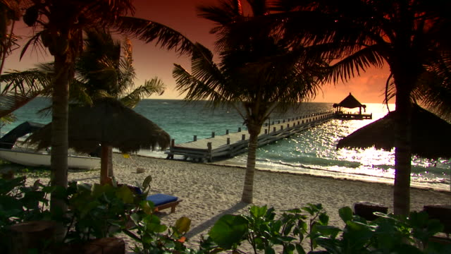 a dock with a hut at the end stretches out into the ocean. - mayan riviera stock videos & royalty-free footage