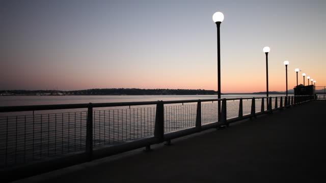 vídeos y material grabado en eventos de stock de a dock with street lights on the seattle waterfront at dusk. - estrecho de puget