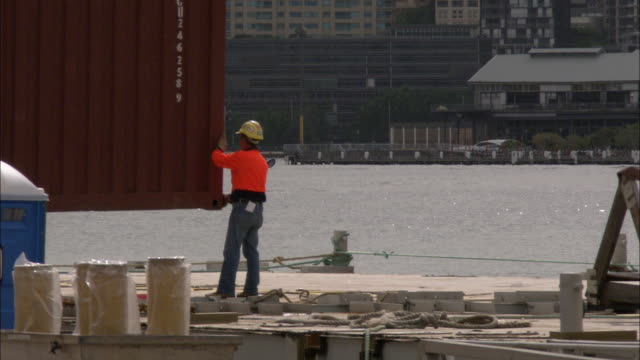 A dock worker guides a metal cargo container into place at Sydney Harbor as a speedboat moves past.