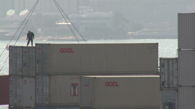 dock worker stands dangerously on shipping containers as crane lifts another container above him, hong kong - pulley stock videos & royalty-free footage