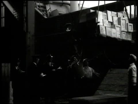 vídeos de stock e filmes b-roll de dock workers placing boxes on hoist boxes hoisted onto ship - 1935