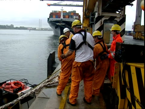 Dock workers pull rope on to quayside, Container Terminal, Southampton, UK