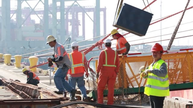 Dock workers wearing hard hats and reflective vests prepare the Port of Long Beach Docks for the delivery of two of the World's Largest ShiptoPort...