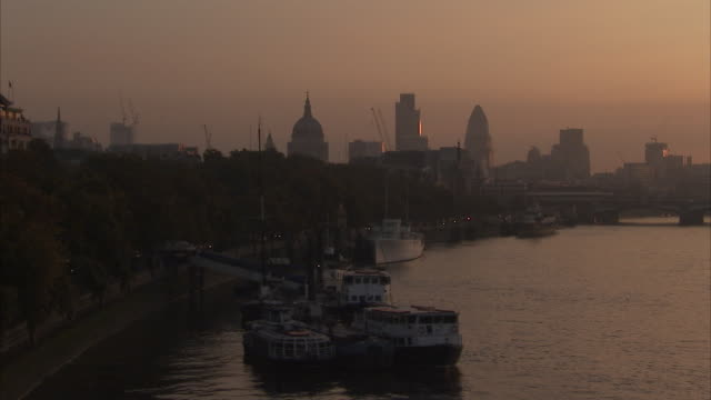 docked boats float at canary wharf on the river thames at sunset available in hd. - morning stock videos & royalty-free footage