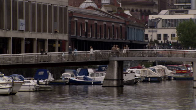 docked boats line bristol harbour near pedestrians and cyclists on a footbridge. available in hd. - bristol england stock videos and b-roll footage