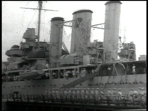 vídeos de stock, filmes e b-roll de docked british submarines soldiers marching on dock near warship submarine moving in water in harbor japanese attacks smoking burned house building... - 1930 1939