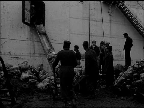 Docked cargo ship armed guards guarding French colonial men unloading bundles MS French soldier holding automatic rifle Workers showing 'papers' to...