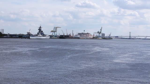 WS Docked cargo ships and Ben Franklin Bridge beyond Delaware River / Philadelphia, Pennsylvania, United States