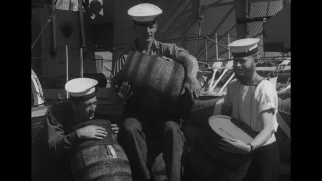docked hmcs athabaskan destroyer, dark smoke / sailors rolling barrels down plank / sailor holding barrel / sailors carrying barrel aboard / sailors... - cayuga stock videos & royalty-free footage