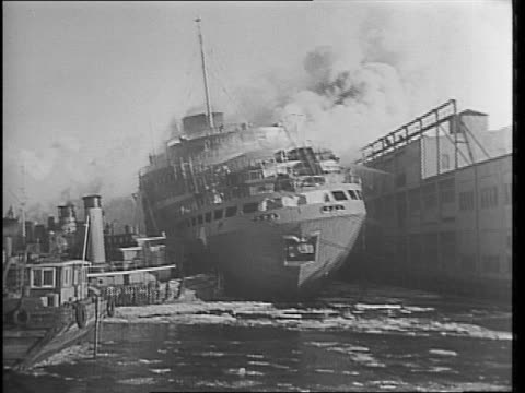 docked in a shipyard in the hudson river a fire burns on the french liner ship ss normandie / multiple views of ship burning / fire engines and... - 1942年点の映像素材/bロール