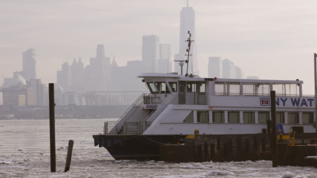 docked water taxi slowly rocks back and forth amidst the snowy and icy hudson river. - water taxi stock videos & royalty-free footage