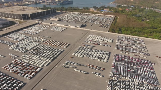 dockside yard full of new cars for import/export with morning sunrise, aerial view - mezzo di trasporto video stock e b–roll