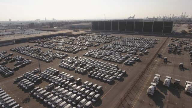朝の日の出、航空写真と輸出入のための新車の完全なドックサイドヤード - 自動車ショールーム点の映像素材/bロール