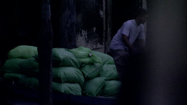 a dockworker moves a cart against large gunnysacks in the early morning. available in hd. - sack stock videos & royalty-free footage