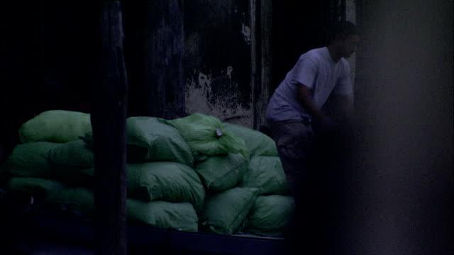 a dockworker moves a cart against large gunnysacks in the early morning. available in hd. - påse bildbanksvideor och videomaterial från bakom kulisserna