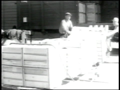 vidéos et rushes de dockworker unloading crates. stern ship. helsinki: aerial helsinki shore. street scene. tram passing. - docker