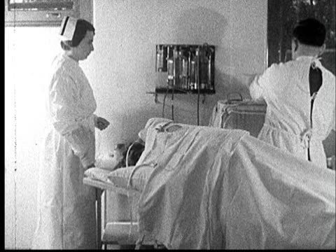 1935 MS Doctor administering pneumothorax treatment to patient covered in sheets/ Doctor injecting air into lung as nurse watches/ AUDIO